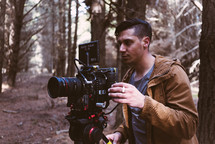 man standing in the woods with a video camera
