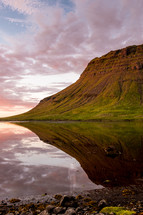 reflection of green cliffs on calm water