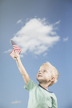 little boy holding an American flag up