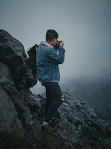 a man taking a picture from a mountaintop