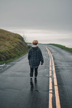 person walking down the middle of a wet road
