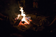sitting by a campfire on a beach
