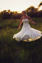 Woman in a white dress twirling in a field of tall grass.