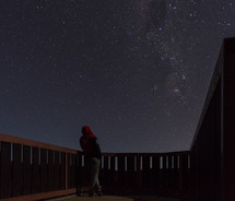man standing on a balcony looking out at stars