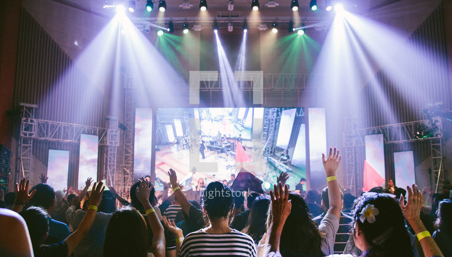 worship leaders on stage leading congregation in music