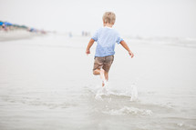 Boy running through the ocean water at the beach.