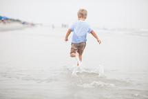 Boy running through the ocean water at the beach.
