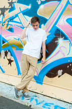 young man leaning on a graffiti covered wall
