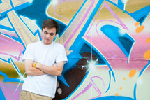 a young man leaning on a graffiti covered wall