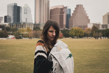 a woman standing in a city park holding a blanket