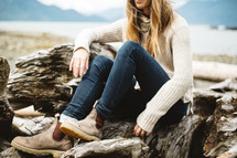 a woman in boots sitting on driftwood on a beach