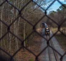 Train on a railroad track as seen through a chain link fence.