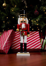 a nutcracker in front of Christmas gifts under a Christmas tree