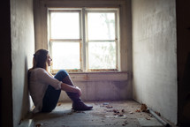 teen girl sitting alone in an empty room near a window