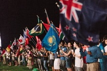 crowd waving flags of various nations