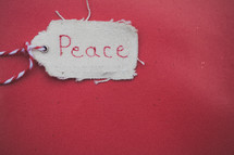 """A Christmas gift tag reading """"Peace,"""" on a red background."""