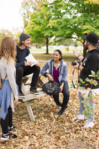 group of friends gathered around a picnic table in fall