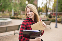 a young woman on campus holding a notebook and journal