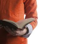 Hands holding an open bible.