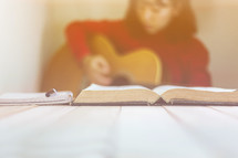 a woman playing a guitar and reading a Bible