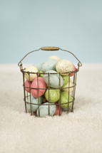 speckled Easter eggs in a wire basket
