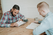 two men reading Bibles and discussing scripture sitting at a table
