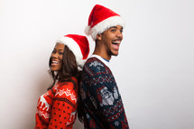 couple in ugly Christmas sweaters and santa hats