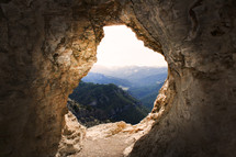 view from the mouth of a mountain cave, looking at distant mountains and forest. Light coming into the cave.