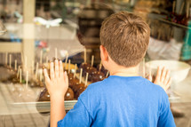 child looking through a window at candy apples
