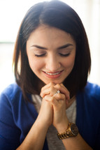 a smiling woman with praying hands