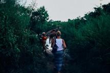 people walking on a wet dirt road