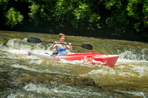 woman kayaking in rapids