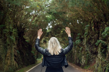 Woman standing on the road in the forest with raised hands.