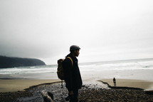 man with a backpack standing on a rocky beach