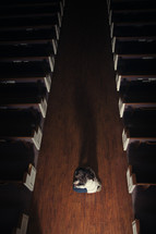 A woman kneeling in the aisle of a church