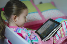 Girl in pajamas reading the Bible on an iPad and smiling. She's reading before bedtime.  Child doing devotions on a tablet. Reading a children's Bible.