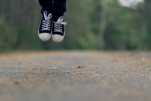 A person's feet jumping above a country road.