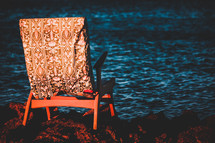 chair on rocks along a shore