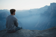 man sitting at the edge of a mountain looking out