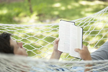 man reading a Bible in a hammock.