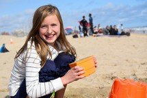 a little girl playing with sand bucket on a beach