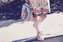 legs of a little girl carrying a lunch box and wearing knee socks