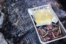 cooking bacon and sausage over a campfire