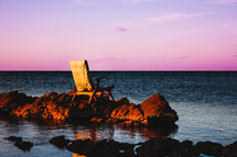 chair on a rock over water