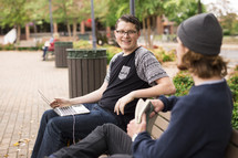 friends sitting on a bench on campus studying and talking before class