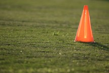 glowing orange cone on a soccer field at sunset