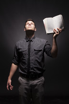 Man holding up Bible with one hand, looking to the heavens for answers,