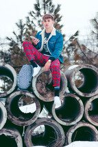teen boy sitting on concrete pipes in winter snow