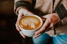 woman holding a cup of coffee with creamer
