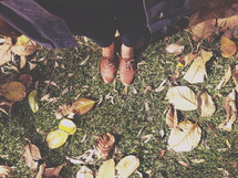 shoes standing in grass and fall leaves